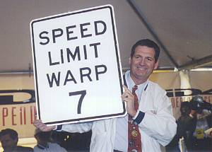 Gov. Miller Holding up SPEED LIMIT WARP 7 sign